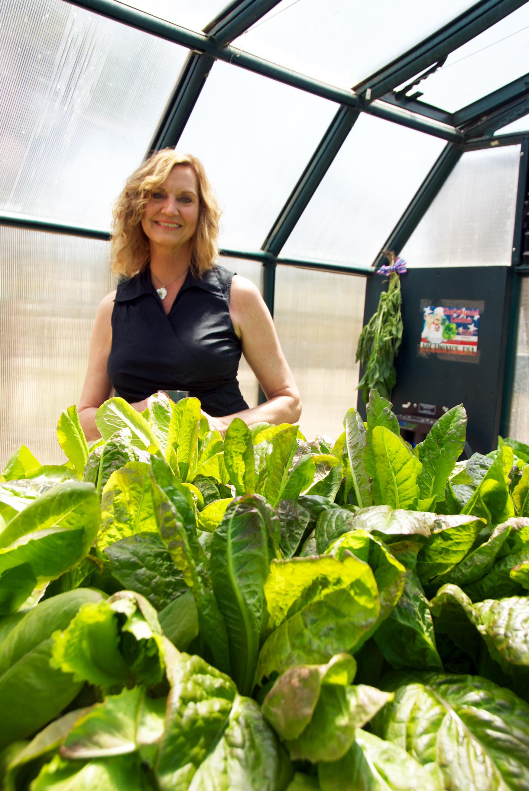 Sue of Sue's Health Foods Store behind Grow Bed #4 verticle